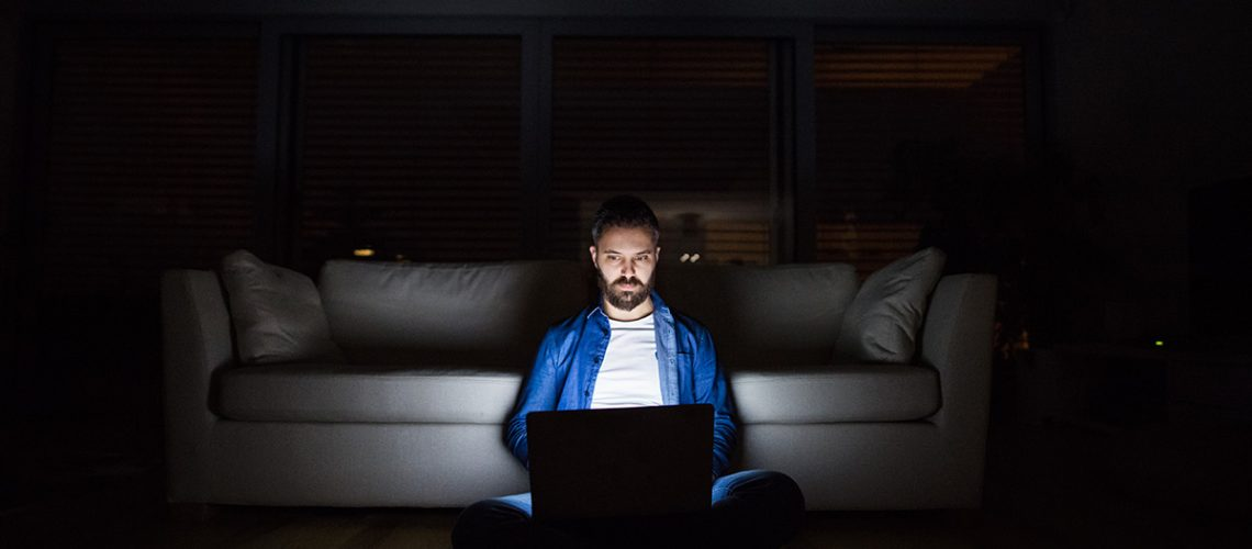 a-man-working-on-a-laptop-at-home-at-night-PHM2BUD