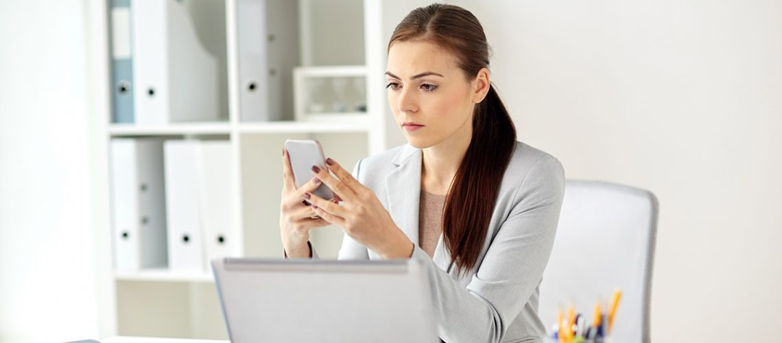 businesswoman-with-smartphone-at-office-PVHB5K8